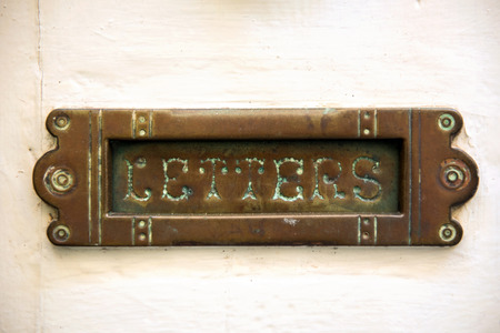 Vintage letterbox on white door in Malta