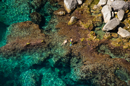 Aerial above view of a couple bathing in the sea