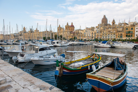 VALLETTA, MALTA - AUGUST 23, 2017: Boats, ships and yachts anchoring in Birgu harbor, one of the biggest port from the Three Cities of Malta