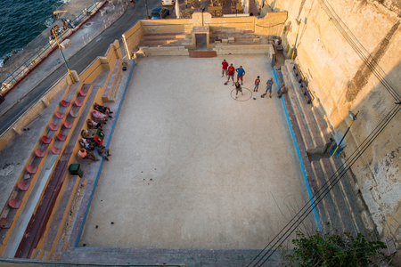 VALLETTA, MALTA - AUGUST 21, 2017: Local residents of Valletta playing bocce (bocci) game in a playground. Bocci is a ball sport closely related to British bowls and French petanque