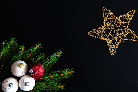 Christmas background with balls, golden snowflake, fir tree branches on black Stock Photo