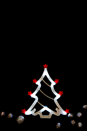 christmas tree shaped led light tube and silver nuts on black stock photo 89222616