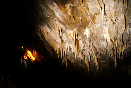Spelunker admiring stalactites in the cave Stock Photo