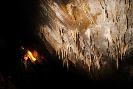 Spelunker admiring stalactites in acave