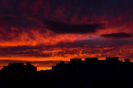 Sunrise in the city. Silhouette of residential apartments, flat of blocks against vibrant red sky