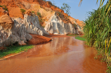 Fairy Stream (Suoi Tien), Mui Ne, Vietnam. The small stream is the place where the desert meets the jungle. Geological attraction with red and white sandstone Foto de archivo