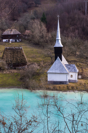 Orthodox church and flooded cemetery next to drowned village at Geamana lake near gold mine of Rosia Montana. Cyanide pollution, turquoise water, ecological disaster, polluted lake with mining residuals Stok Fotoğraf