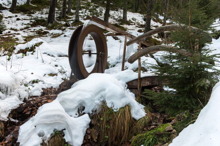 Functional small water mill wheel in the forest at winter
