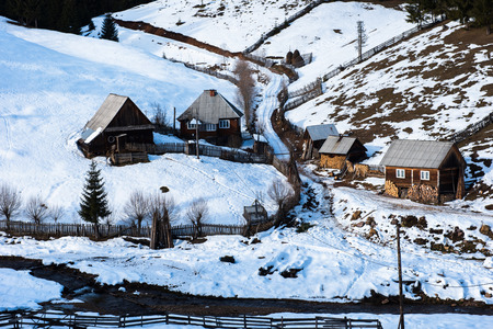 Traditional homestead with wooden houses at winter in Transylvania, Romania