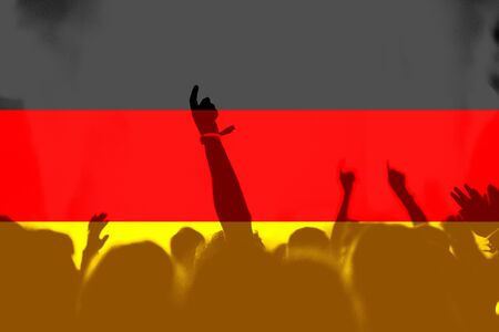 Crowd of football, soccer fans with raised arms with blending Germany flag