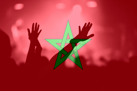 Crowd of football, soccer fans with raised arms with blending Morocco flag Stock Photo