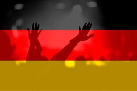 Menge des Fußballs, Fußballfans mit den angehobenen Armen mit der Mischung von Deutschland-Flagge Standard-Bild - 94295744