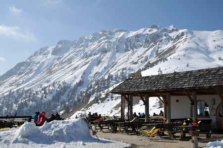 ARABBA, ITALY - MARCH 7, 2011: Skiers and snowboarders enjoying a coffee and sunbathing outdoor at a restaurant in the Italian Dolomite mountains