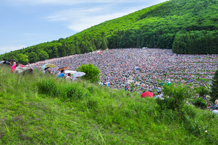 SUMULEU CIUC, ROMANIA - JUNE 6, 2014: Hungarian Catholic pilgrims, crowd of people gathering in Csiksomlyo to celebrate the Pentecost. The religious event is a symbol of Szekler national identity