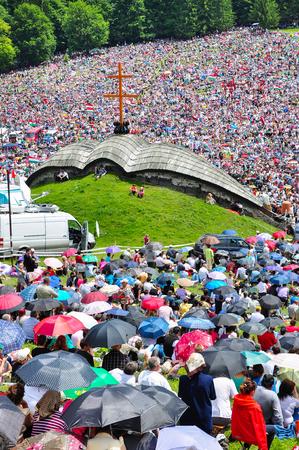SUMULEU CIUC, ROMANIA - JUNE 6, 2014: Hungarian Catholic pilgrims, crowd of people gathering in Csiksomlyo to celebrate the Pentecost. The religious event is a symbol of Szekler national identity