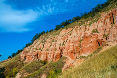 Succession of red and white clays with dinosaur fossils. Geological reserve of Rapa Rosia, Romania Stock Photo