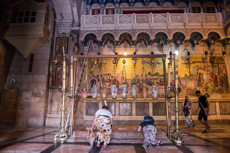 JERUSALEM, ISRAEL - MAY 15, 2018: Pilgrims worshipping the Stone of Unction, the place where the body of Jesus was laid down, after the crucifix. Church of the Holy Sepulchre