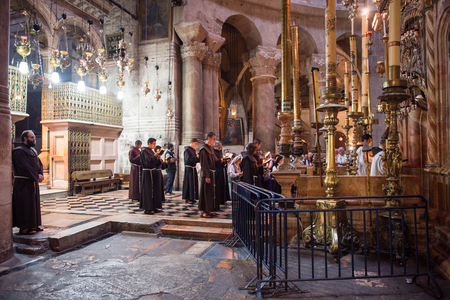 JERUSALEM, ISRAEL - MAY 15, 2018: Franciscan monks praying in the front of Jesus tomb in the Church of the Holy Sepulchre