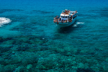 AYIA NAPA, CYPRUS, JUNE 15, 2017: Tourist boat approaching the sea caves of Ayia Napa from the sea. The littoral caves are one of the major tourist attractions of the island of Cyprus Éditoriale