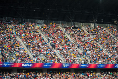 CLUJ, ROMANIA - JUNE 16, 2018: Crowd of people, soccer fans in the tribune supporting their favorites at a match between Romania Golden Team and Barcelona Legends Editorial