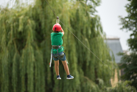 CLUJ, ROMANIA - JUNE 17, 2018: Child descend on a zipline in the park during the Sports Festival