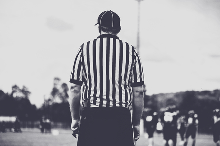 American Football  line empire, referee supervise a match. Toned image