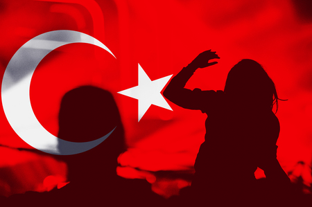 Crowd of people with raised arms over blending Turkey flag
