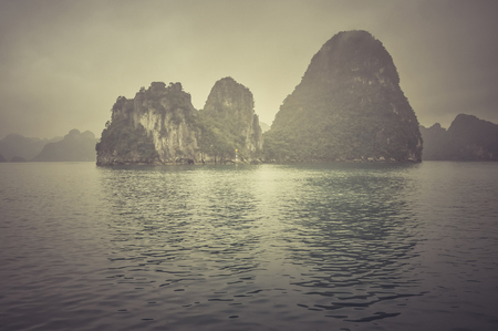 Misty Halong bay (Ha Long), Vietnam, in a rainy day. Filtered and toned image