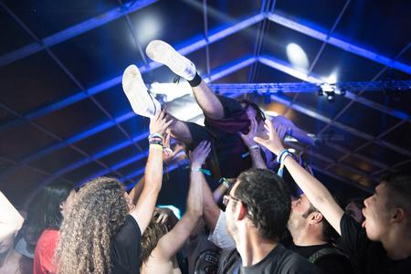 BONTIDA, Rumania - 22 de julio de 2018: Chico haciendo multitud de surf, escenario de buceo durante un concierto en vivo de Cancer Bats en el festival Electric Castle