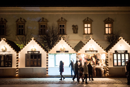 CLUJ NAPOCA, ROMANIA - DECEMBER 30, 2017: Cheerful people enjoying the Christmas market at night in the center of the old city and buying presents and goodies