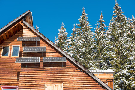 Solar panel on a wooden lodge in the forest at winter