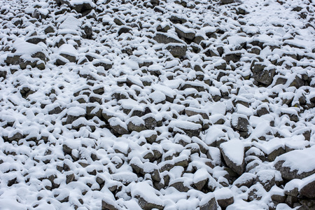 Scree slope, debris, stones covered with snow in the mountains