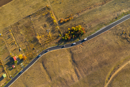 Aerial drone view of winding asphalt road at autumn Standard-Bild