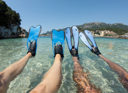 Snorkeler couple relaxing on the beach. Tanned legs in blue fins, flippers in crystal clear sea water Stock Photo