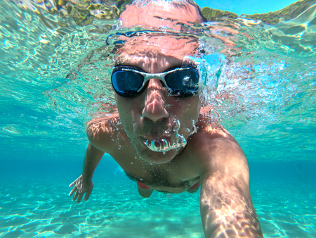 Underwater view of a young diver man swimming in the sea. Air bubbles coming out from mouth and nose 写真素材 - 118792655