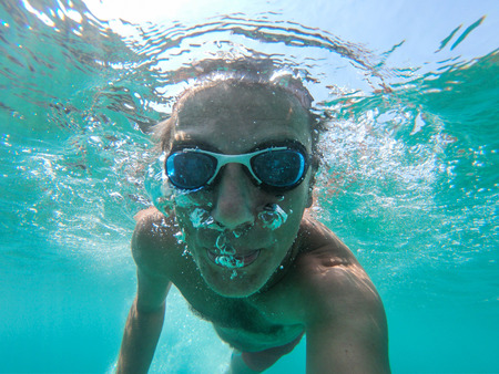 Underwater view of a young diver man swimming in the sea. Air bubbles coming out from mouth and nose