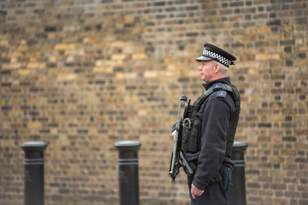 LONDON, UK - MARCH 22, 2019: Armed British police officer on duty patrolling and preventing terrorism attacks on the streets of the city