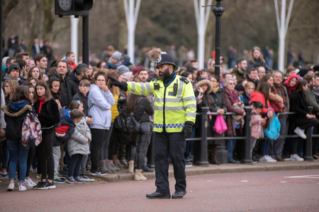 LONDON, UK - MARCH 22, 2019: Metropolitan Police Officer patrolling near the Buckingham Palace during the Chaning the Guards Parade Editorial