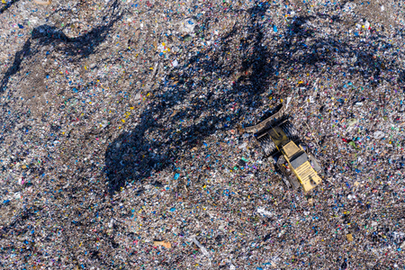 Aerial top drone view of large garbage pile, trash dump, landfill, waste from household dumping site, excavator machine is working on a mountain of garbage. Consumerism and contamination concept Foto de archivo