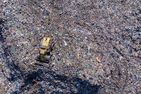 Aerial top drone view of large garbage pile, trash dump, landfill, waste from household dumping site, excavator machine is working on a mountain of garbage. Consumerism and contamination concept Reklamní fotografie