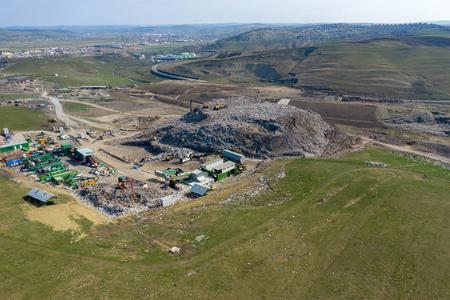 Drohnenansicht von oben auf großen Müllhaufen, Mülldeponie, Deponie, Abfall von der Hausmülldeponie, Baggermaschine arbeitet an einem Müllberg. Konsum- und Kontaminationskonzept