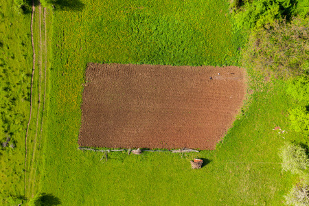 Aerial view of a plowed agricultural field in the middle of a meadow Imagens