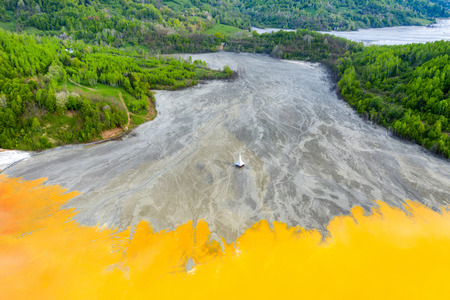 Aerial view of Geamana church, Romania flooded by copper mining waste water. Acid yellow fluids from a drone