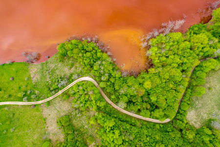 Aerial view of colorful red copper mining waste water in contrast with fresh green forest by drone