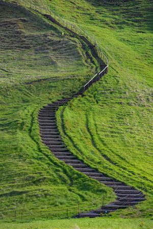 Small path leading up a green hill near Skogafoss waterfall, Iceland