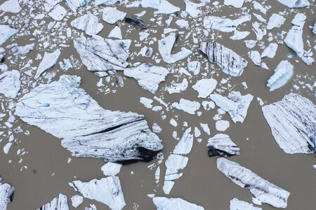 Aerial view of floating icebergs as a result of global warming in Fjallsarlon glacier lake in Iceland by drone