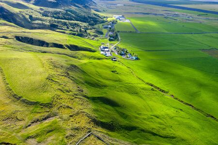 Aerial view of Icelandic farm houses and green countryside hills. Skogar, Iceland from a drone