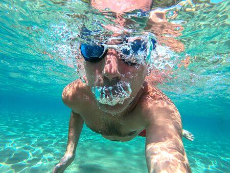 Lustiger Kerl, der Spaß hat und Unterwasser-Selfie beim Schwimmen im Meer macht