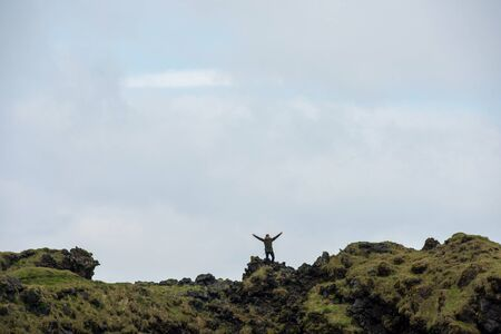 LONDRANGAR, ICELAND - MAY 19, 2019: Tourist posing on the top of the Londrangar basalt cliffs in the Snaefellsnes paninsula, Iceland
