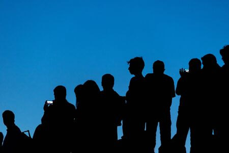 Silhouette of concert crowd against blue sky